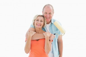 Happy older couple holding paint roller on white background